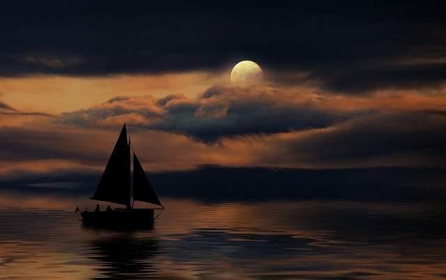 A sailboat is hidden in the shadows on the water.  The moon is in the night sky above.  Boating at night is not for the faint of heart.