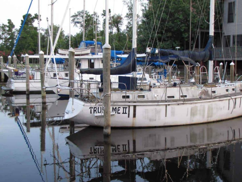 A series of sailboats sit moored to their slips in this photo.