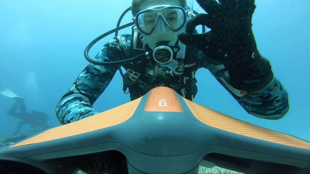 A diver shows their happiness using the Geneinno S1 underwater scooter in this image.