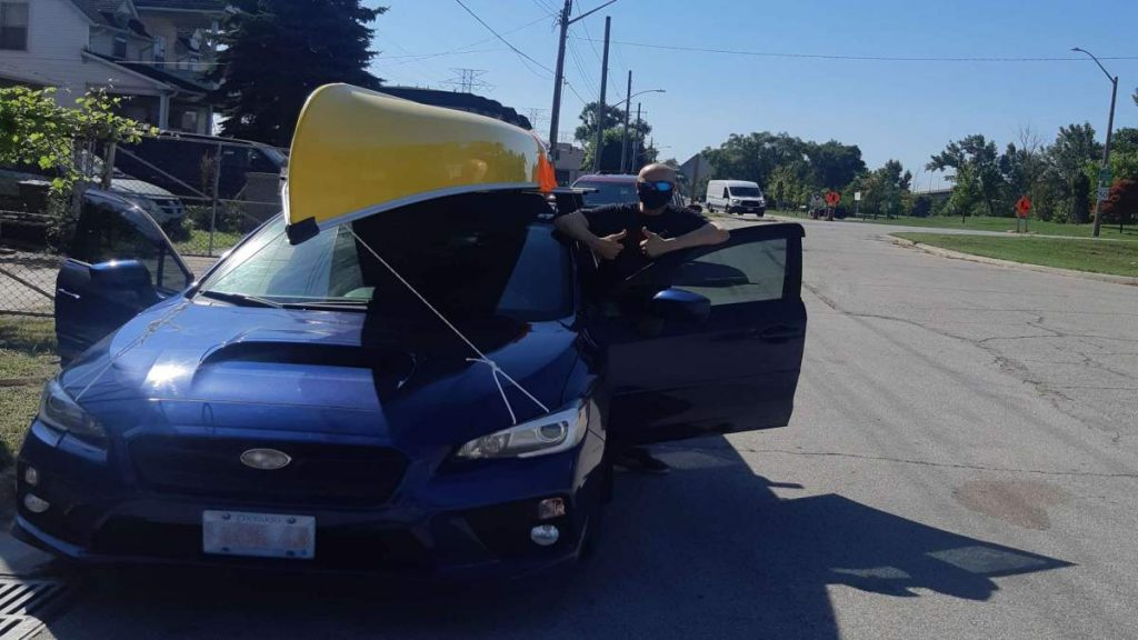 A picture of Jeremy Shantz standing by his car with his yellow Kevlar canoe strapped to the roof rack.