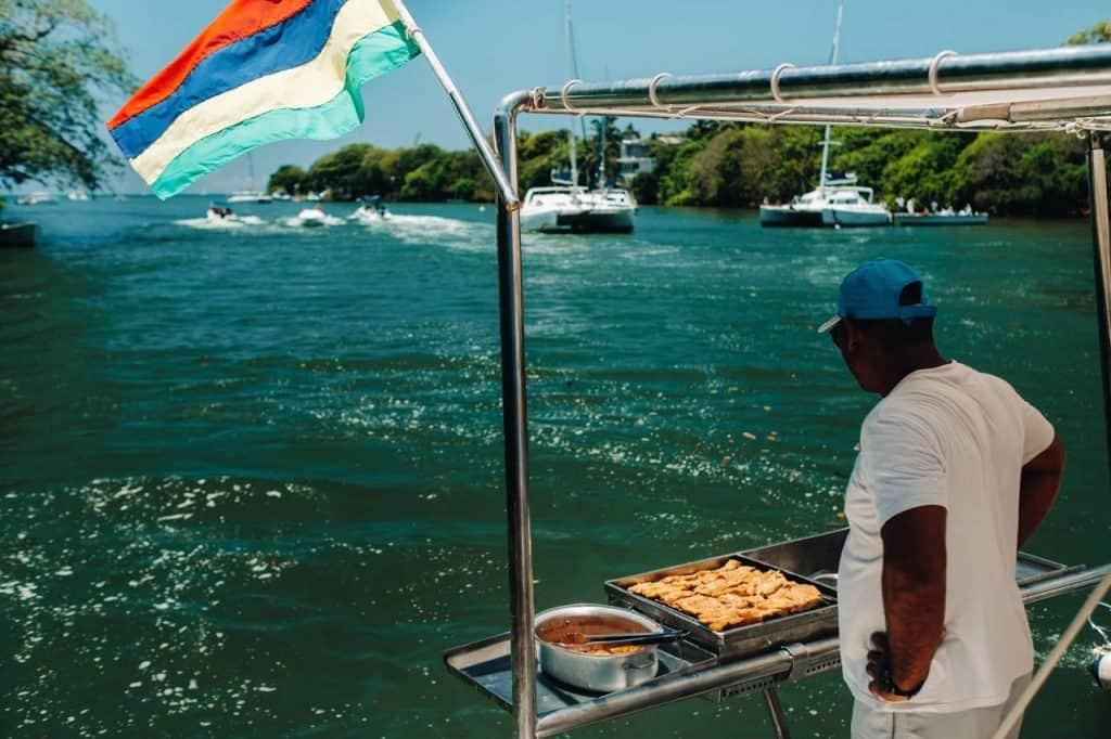 A man cooks a feast aboard his watercraft.