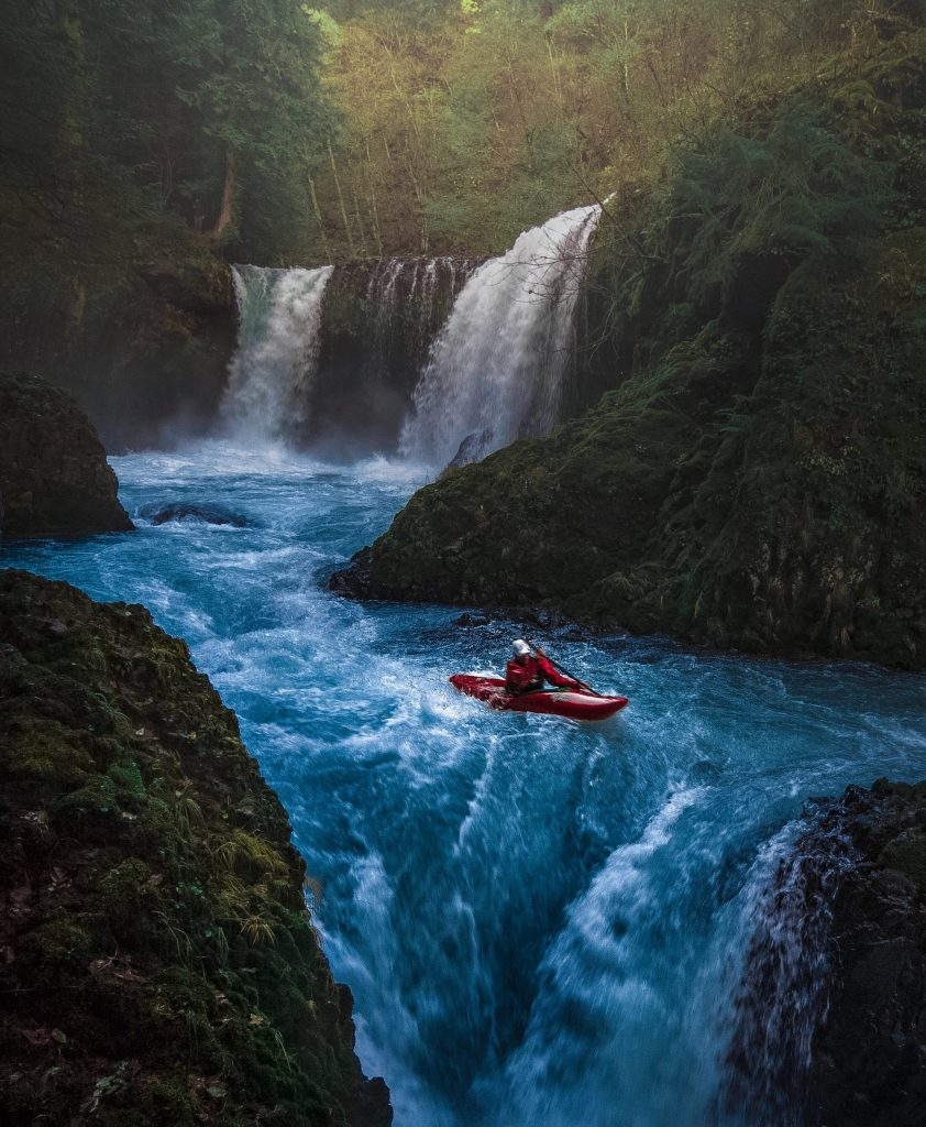 A Kayak rides in rough waters.