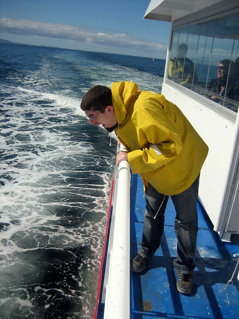 A man is sea sick and vomits overboard while on board a catamaran.