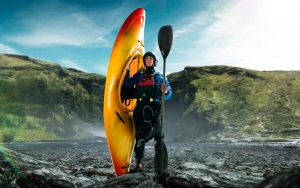 A kayaker holds up his kayak while out on expedition.