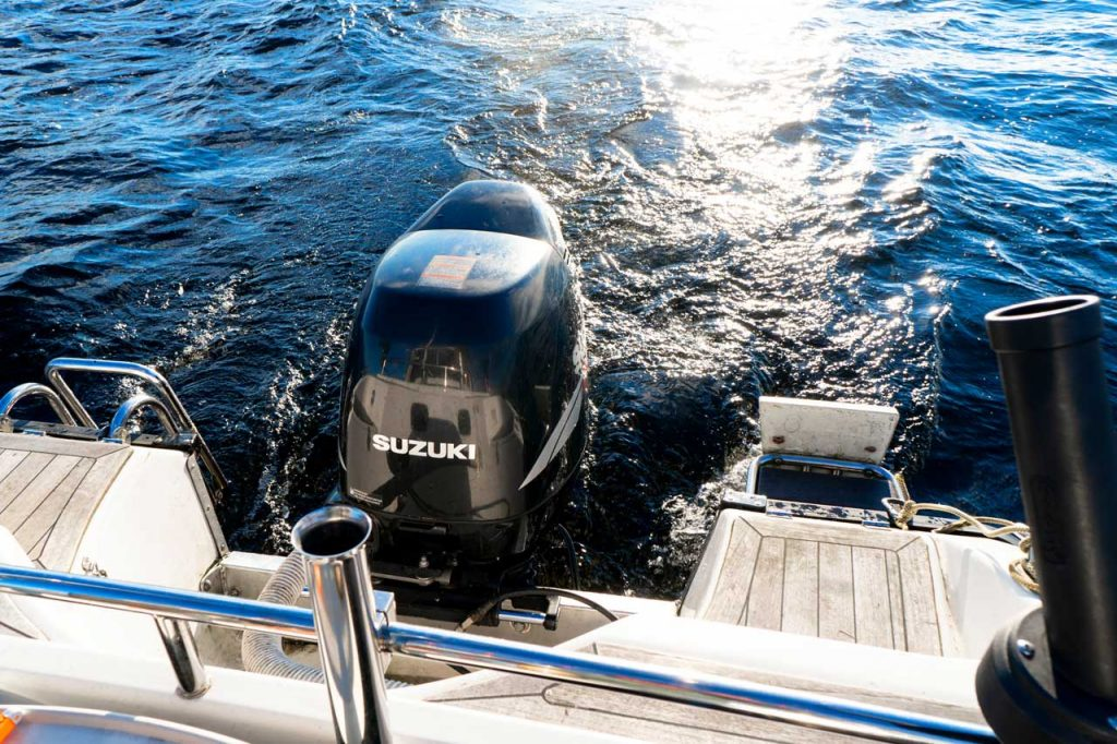 A Suzuki outboard engine is shown operating attached to the rear of a boat.