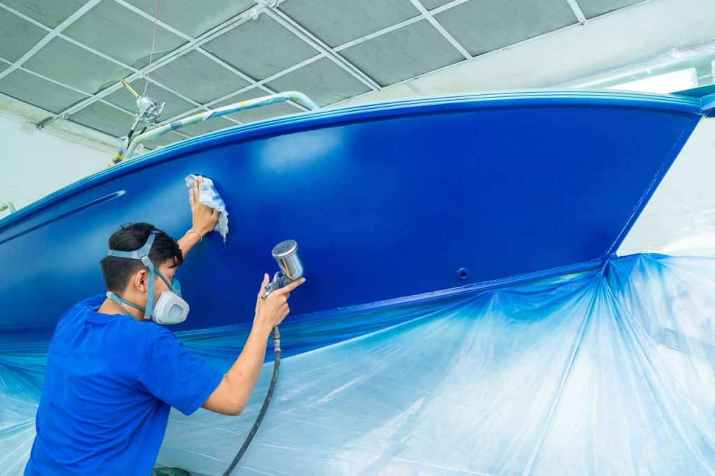 A man works on re-painting his boat hull.