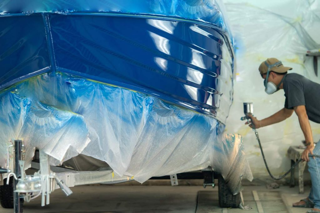 A man uses air compression to paint a boat hull in this file photo.