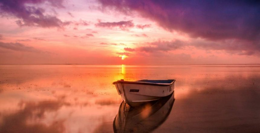 A v-hulled small boat sits peacefully at sunset in this photo.