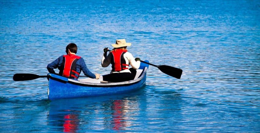 Two people paddling out in a canoe